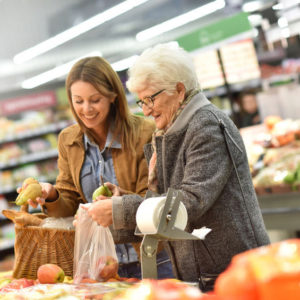 Young woman helping older woman do grocery shopping.